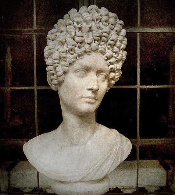 A bust of a Flavian woman. The fashionable style among women during the reign of the Flavians involved hairpieces and wigs to create a stack of curls on the crown of the head.