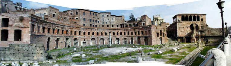 Picture of Trajan's Markets as they appear today. In the foreground lay the remains are that of an open courtyard littered with stone ruins. In the background are the remains is a partially spherical two-storied building that once served as the Roman marketplace.
