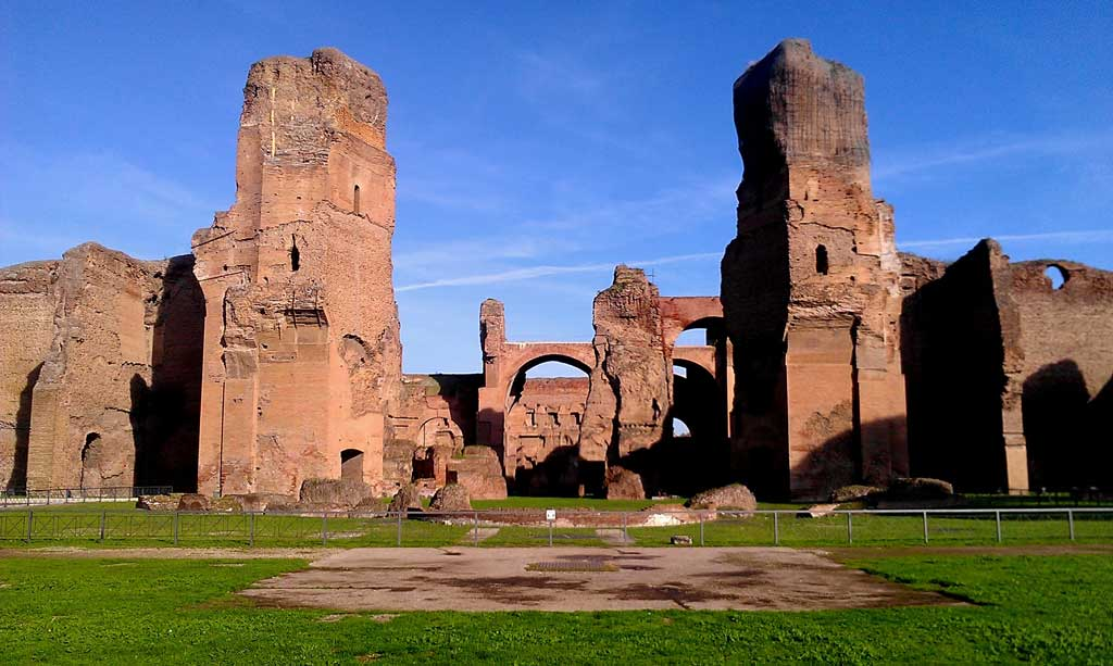 Picture of the outer remains of the Baths of Caracalla. In the foreground, there is an open courtyard leading up towards the entrance to baths. In the background are the remains of the baths themselves, with two large towers standing at the entryway of the principle facade and the great courtyard just beyond it.