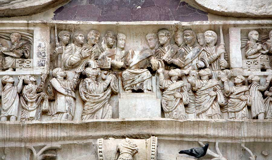 This photo shows a detail of the northern frieze of the Arch of Constantine. This detail shows Constantine distributing gifts from his throne down to his supporters.
