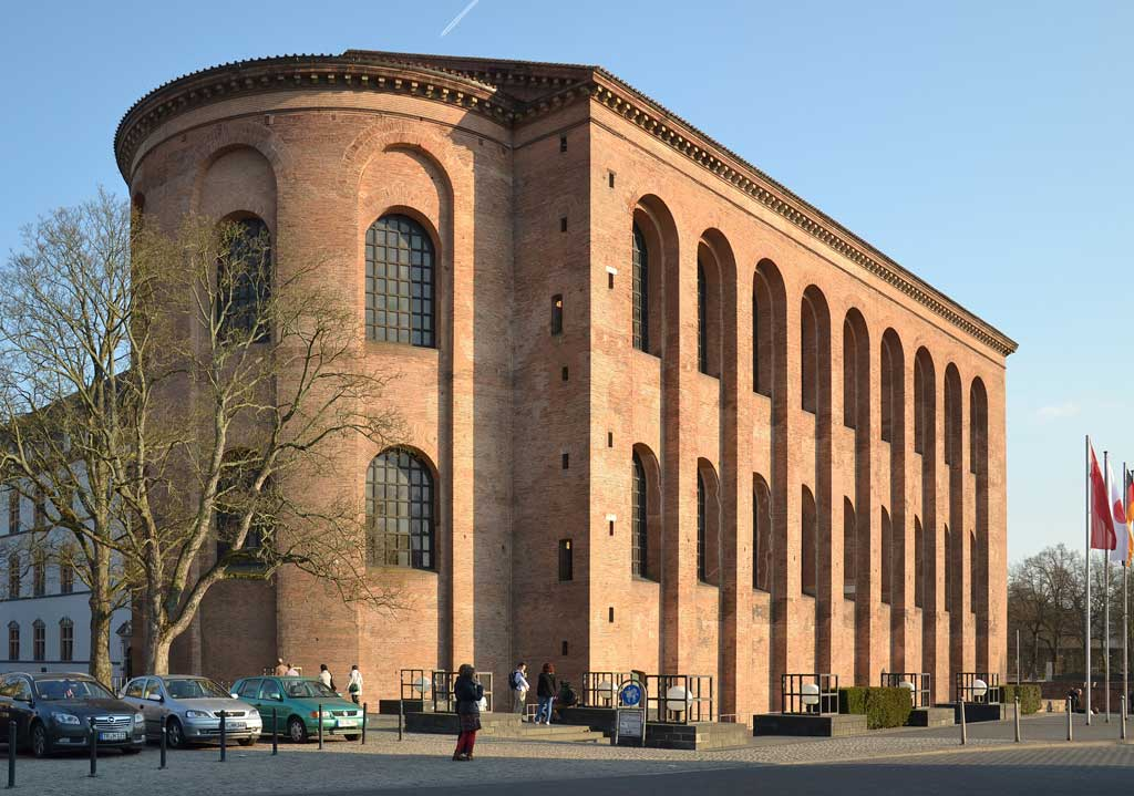 Picture of the exterior of the Aula Palatina, detailing a rounded nave and the outer facade of the building. There are two rows of windows on the exterior of the Aula Palatina, each in the shape of the Roman arch. This is an exterior photo of Aula Palatina, known today as the Church of the Redeemer in Trier, Germany, circa 310 CE.