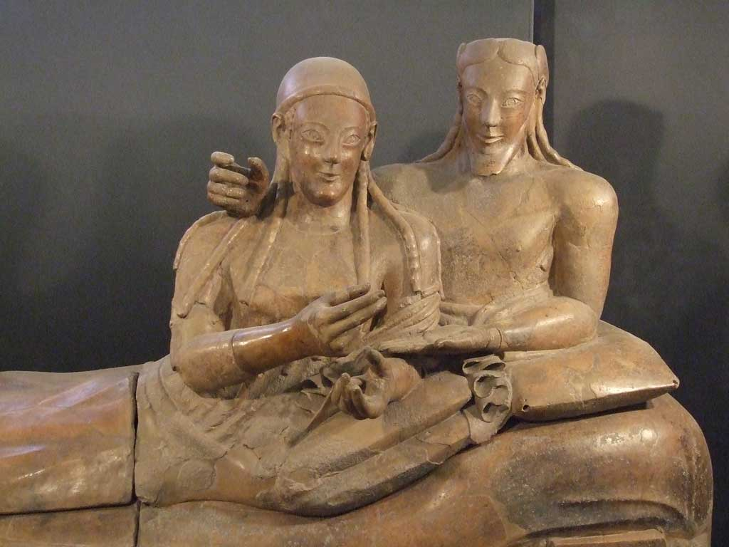 Picture of husband and wife laying side by side atop the terra cotta sarcophagus.