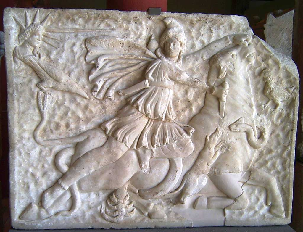 Marble relief illustrating the go Mithra slaying a bull. Stationed around Mithra are other beasts. A scorpion and dog are at the bottom of the relief while a snake intertwines around the bull.