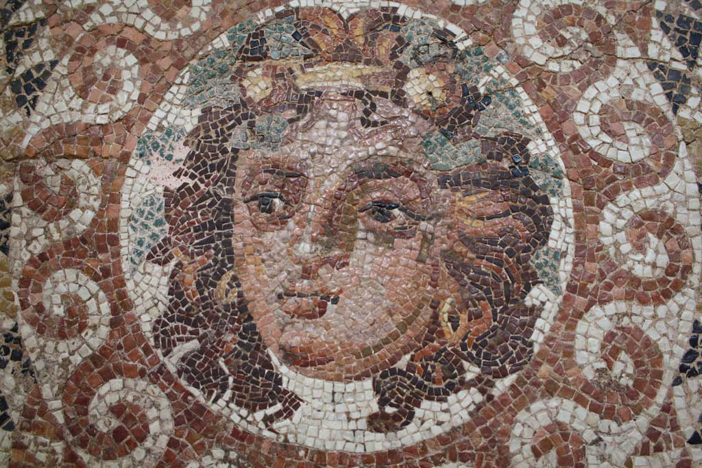 A tiled frieze of the bust of Dionysus. In this image, the viewer sees the long-haired deity with vines surrounding his head.