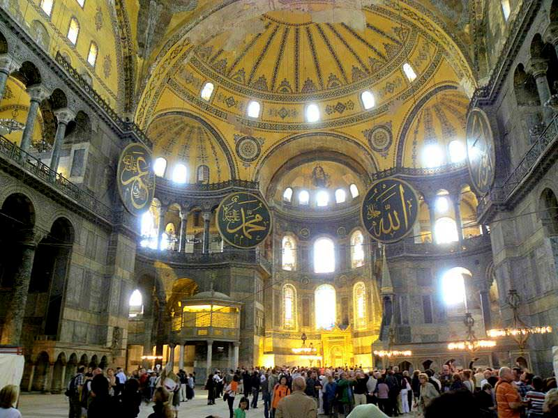 Interior picture of the sanctuary apse within the Hagia Sophia. From this vantage, one sees the Arabic roundels at each corner of the edifice's second floor along with the uncovered Christian iconography at the center of the apse.