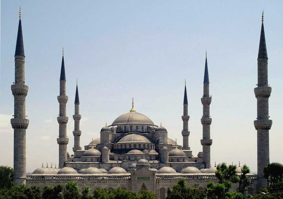 Picture of the Suleiman Mosque in Istanbul, Turkey. Sometimes called the Blue Mosque because of its blue hue, the edifice includes a stacked layer of domes with a singular dome at its top. Six large minarets, three on each side, surround the edifice.