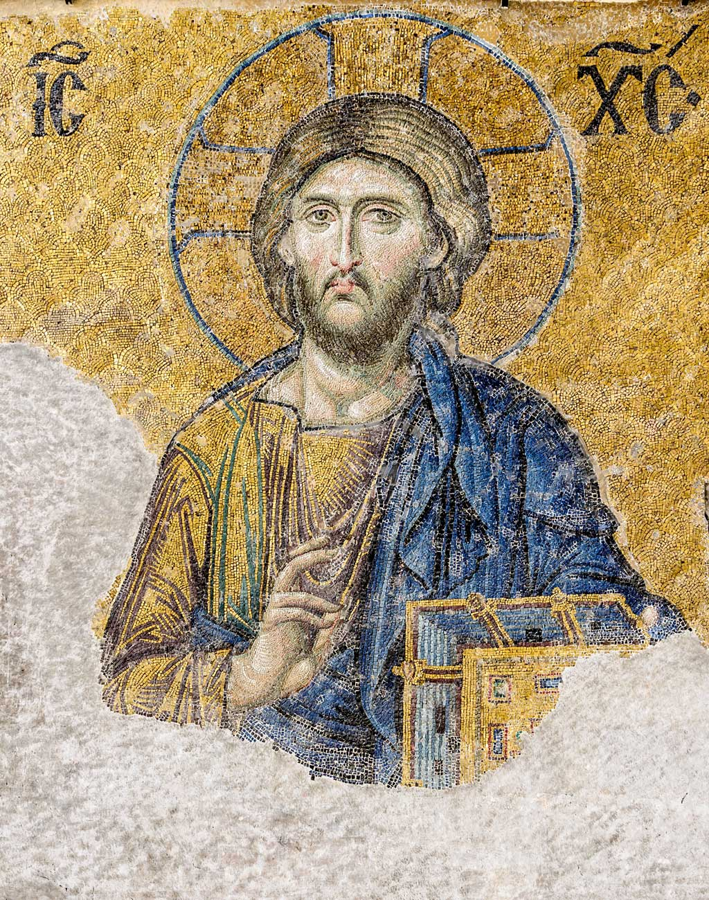 Image of Jesus found within the Hagia Sophia. Carrying a gold-covered New Testament, Jesus looks forward at the onlooker giving a gesture of blessing with his left hand. On either side of the icon are both halves of the Greek Christogram which together spell Jesus Christ.