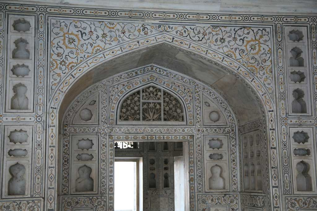 Picture of a doorway at the Mughal Agra Fort, India. The doorway includes elaborate geometric inlays around the outer edges of the door along with intertwined plant designs.