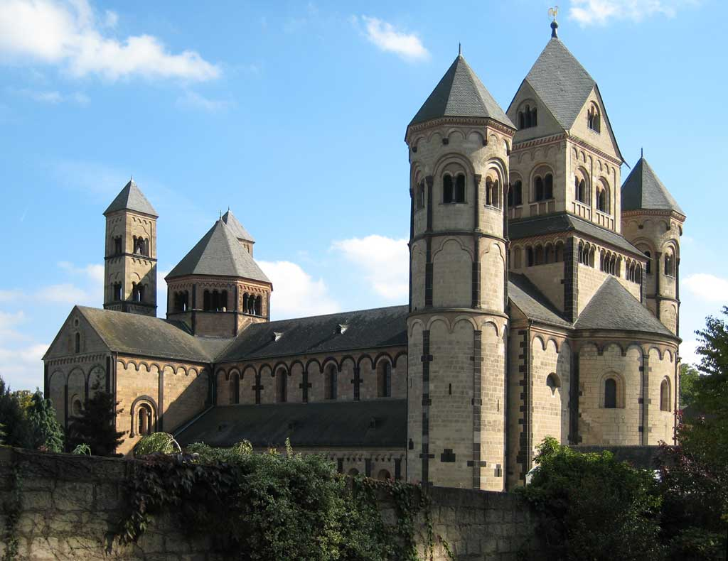 Picture of Maria Laach Abbey in Germany. From the outside, one sees three large towers that welcome visitors into the cathedral. A long nave follows with the chancel in the rear of the cathedral.
