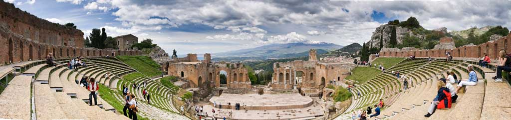 A contemporary photograph of a panoramic view of the ancient Greek theatre in Taormina, Sicily, Italy.