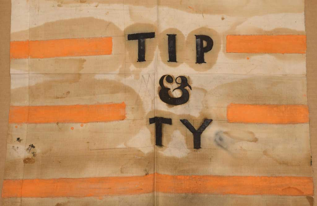 A campaign banner with a variation of the Tippecanoe and Tyler too slogan, used in the 1840 U.S. presidential campaign. Brown sign with black lettering 'TIP & TY' and orange stripes in background.