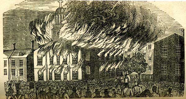 Church in flames with people gathered around