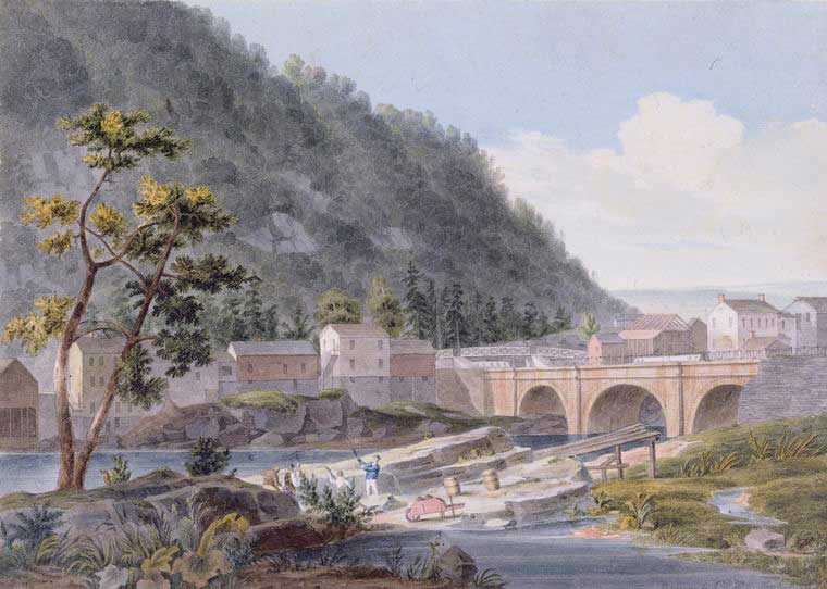 Bridge over the Erie Canal with buildings and a hill behind it