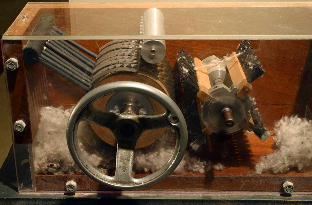 A cotton gin on display at the Eli Whitney Museum showing the internal mechanisms and seeds being stripped from cotton.