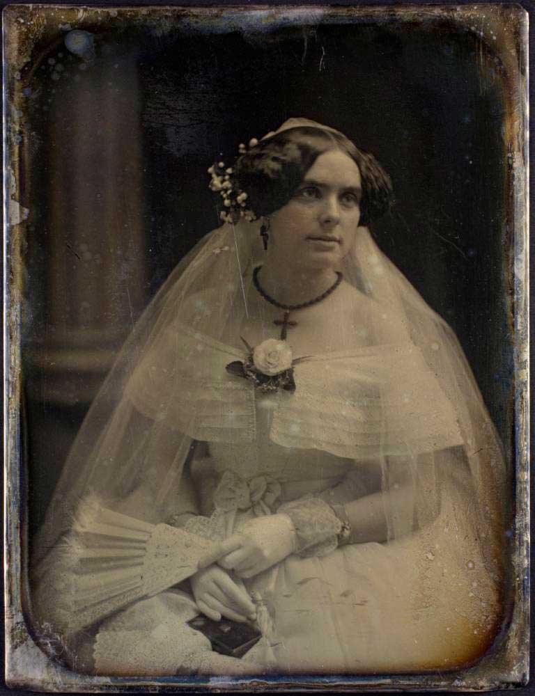 Old photo of a bride wearing a wedding dress and veil, holding a fan