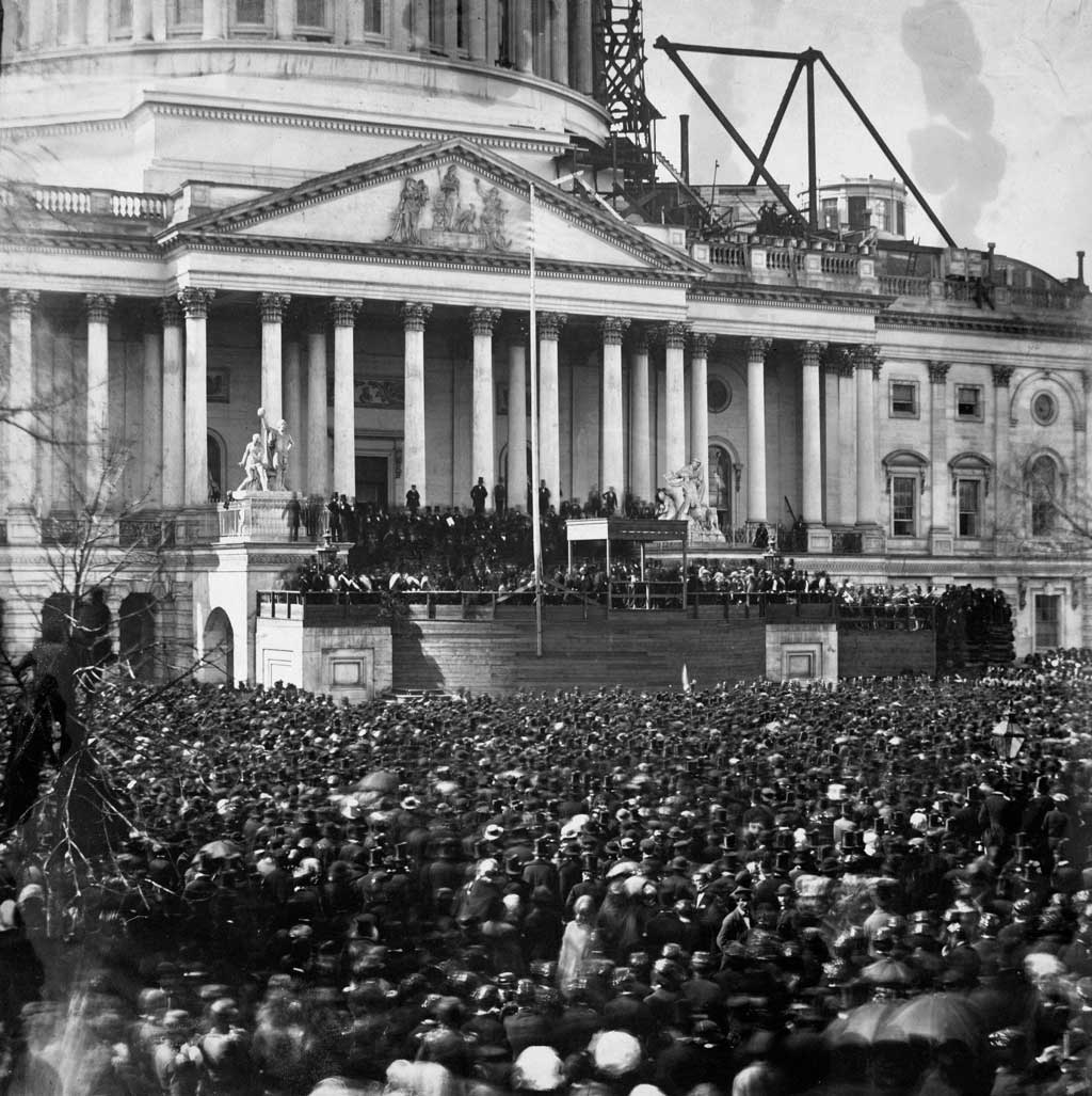 Photograph shows participants and crowd at the first inauguration of President Abraham Lincoln, at the U.S. Capitol, Washington, D.C. Lincoln is standing under the wood canopy, at the front, midway between the left and center posts. His face is in shadow but the white shirt front is visible.