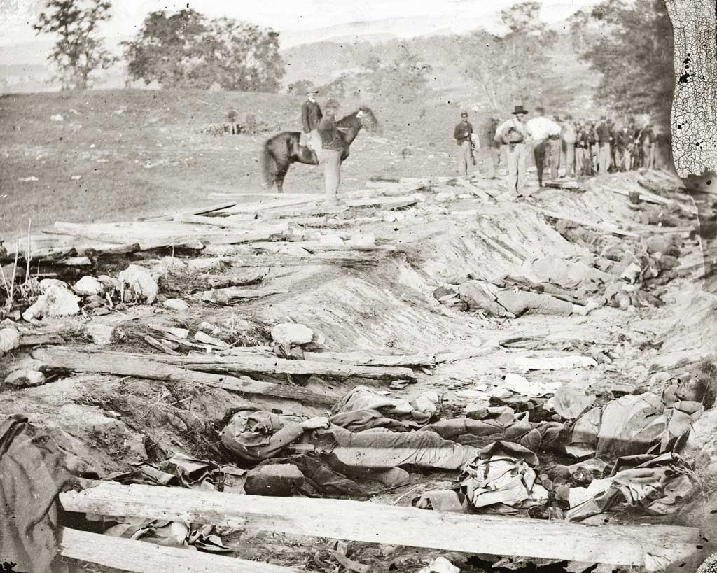 Confederate dead at Bloody Lane, looking northeast from the south bank; the Union soldiers looking on were likely members of the 130th Pennsylvania, who were assigned burial detail