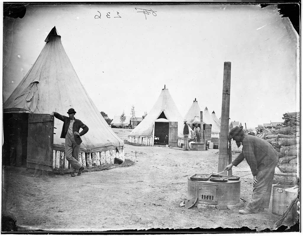 Civil War soldiers preparing a meal in camp. Cooks work on makeshift stoves while other look on from tent barracks.