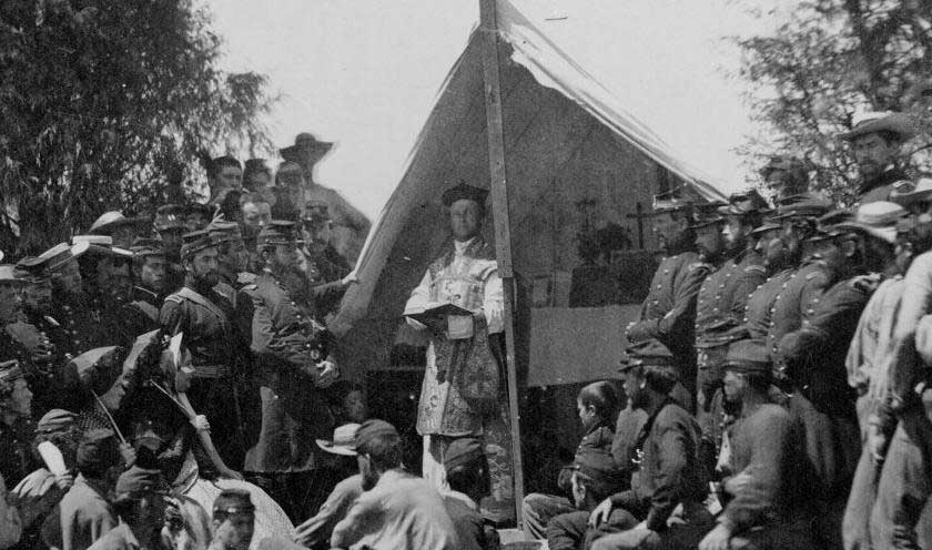 Sunday morning mass in camp of 69th N.Y.S.M. Chaplain reading, surrounded by soldiers in uniform.