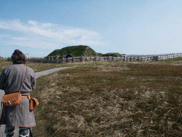 Photograph of a reenactor surveying the Viking colonisation site at L'Anse-aux-Meadows, Newfoundland, Canada