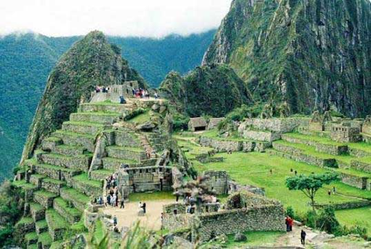 Photograph of the Central Square of Machu Picchu, showing terraces, homes and people.