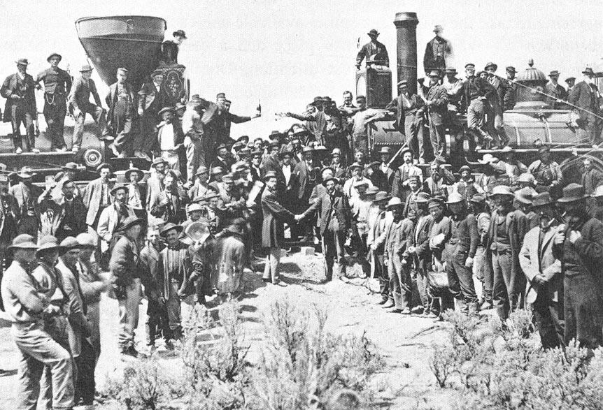 Dozens of men surround 2 trains - one from the east and one from the west. The mood of the image is celebratory. Some men have climbed up onto the engines. Two men reach across the gap - one with champagne and the other with wine glasses. In the foreground two men stand on the ground shaking hands.