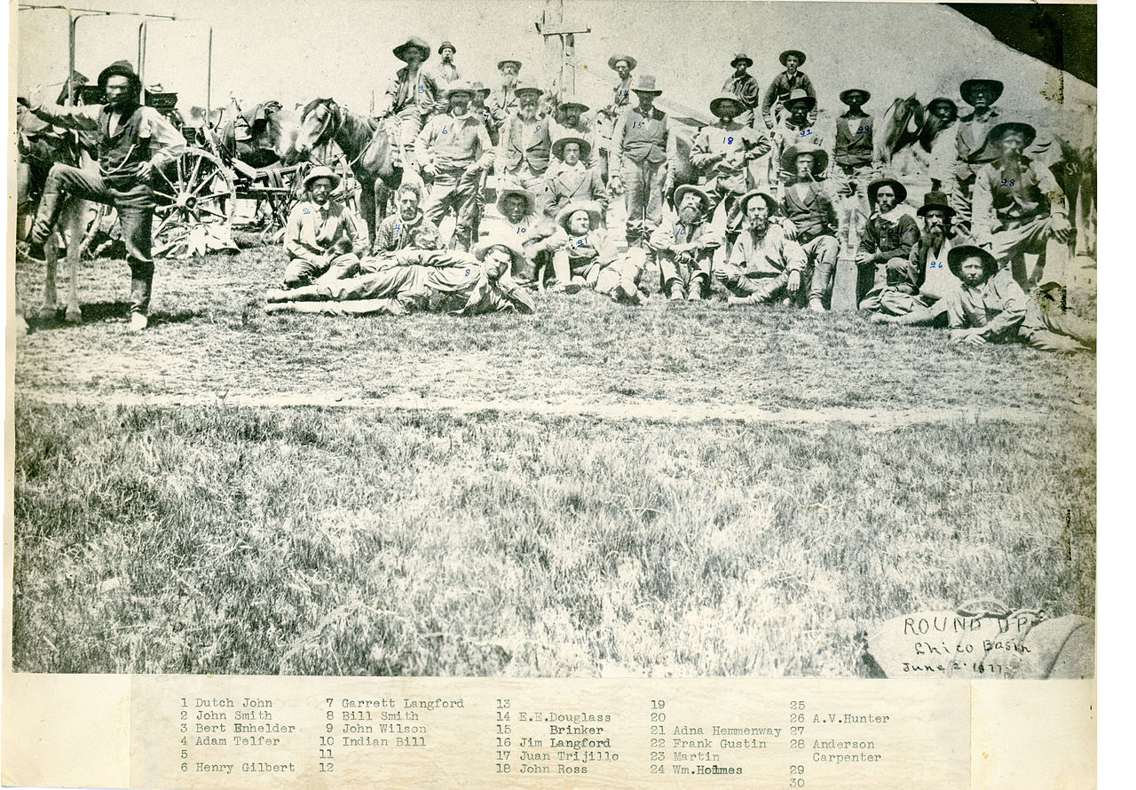 Thirty men sitting, standing and laying at a ranch. Two horses and a wagon are also in the picture.