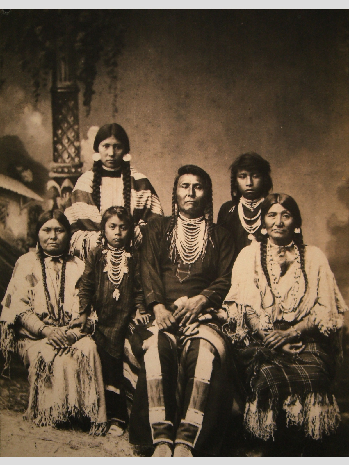 Chief Joseph is seated in the middle of the photo. He is surround by five family members — two of whom are small children.