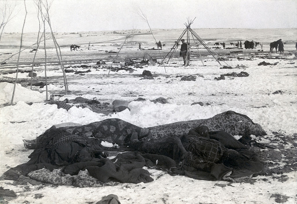 A winter scene on the prairie. Four shapes wrapped in blankets are in the foreground. Soldiers and horses are standing in the background. One man stands inside teepee poles and looks toward the camera.