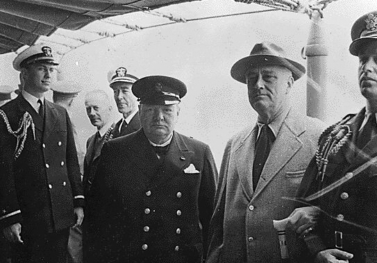 Winston Churchill standing to the left of Franklin Roosevelt on board a ship.