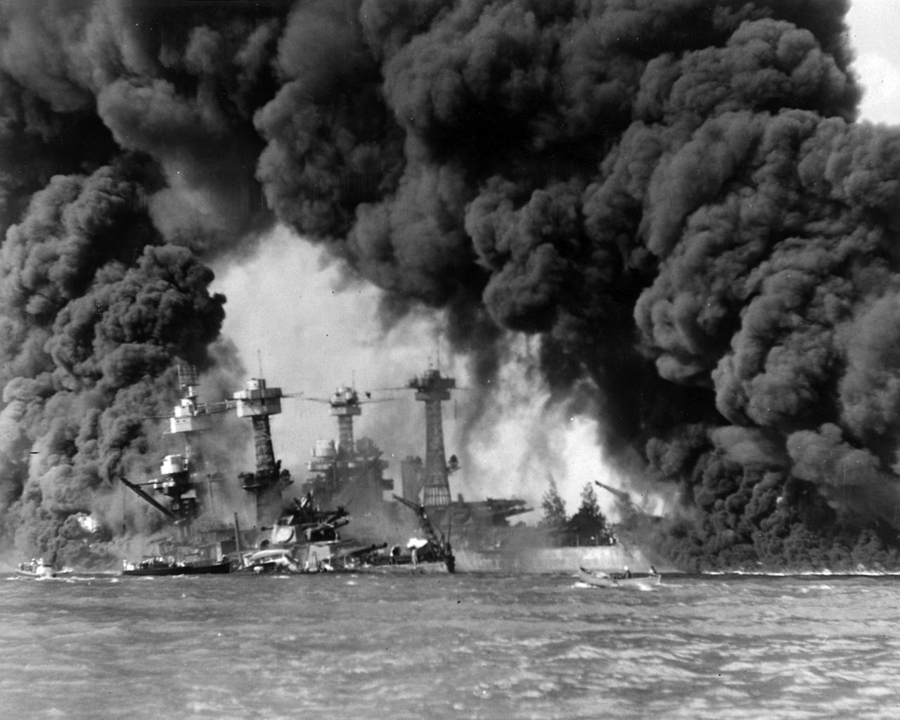 Dark smoke and flames billow over the remains of navy ships while small boat loads of sailors look on.