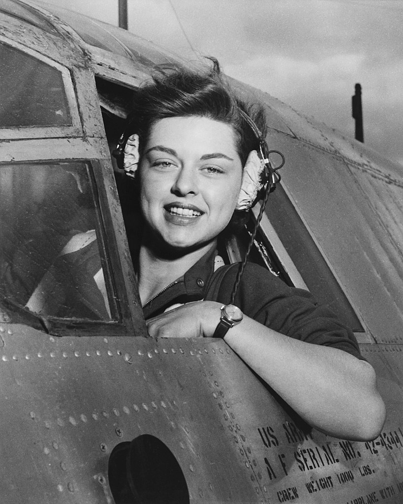 Woman, Elizabeth Gardner, sits in the cockpit of an aircraft. her arm and head are outside of the aircraft window. She is wearing headphones.