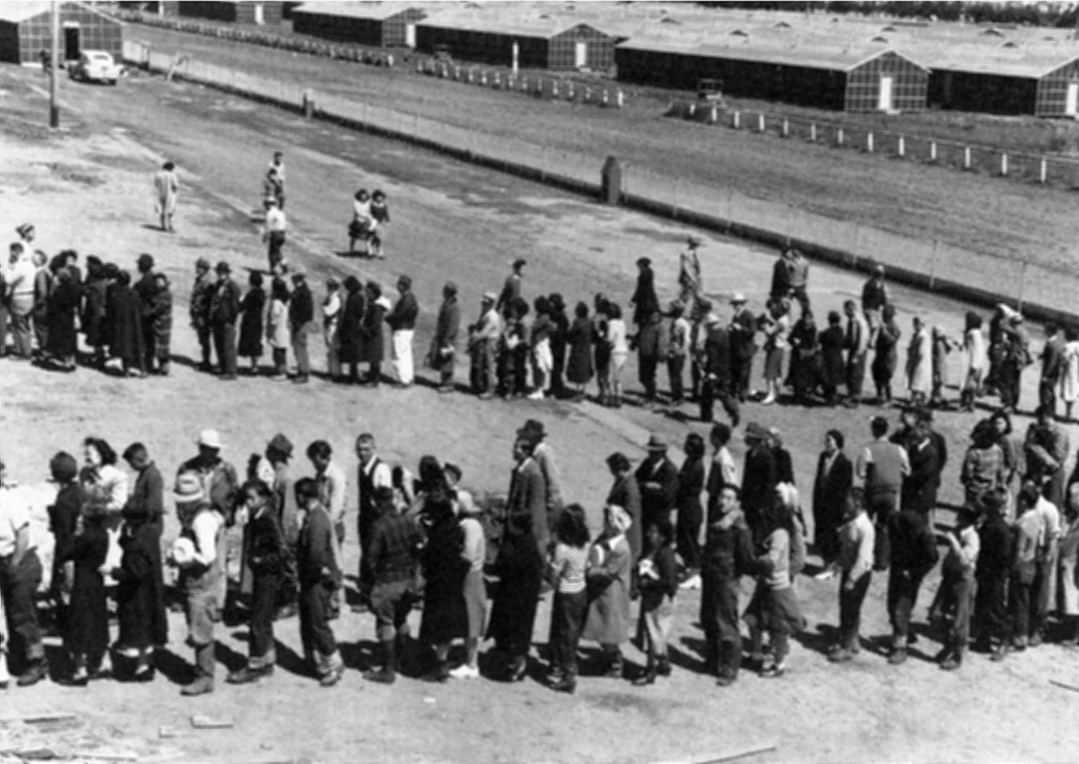 Two long lines of people waiting. Long residence buildings are in the background.