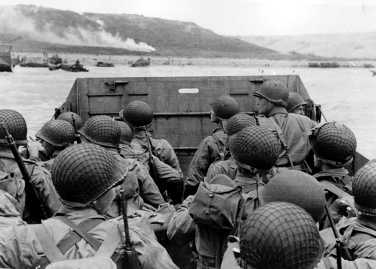 The camera faces the backs of sixteen soldiers in combat gear in LVCP (Higgins boat). Several of the young men look over the bow of the boat to access the fighting occurring near the shoreline.