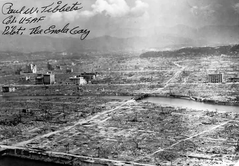 Landscape of a city flattened to almost nothing. A river runs through the middle of the desolation. Only about a dozen buildings are standing.