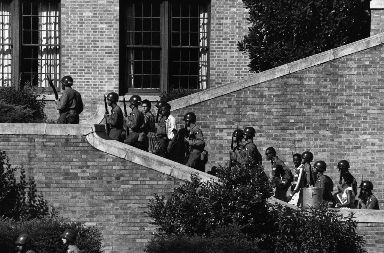 Black and white photo shows eleven armed soldiers escorting five African American high schoolers up the steps of a building.