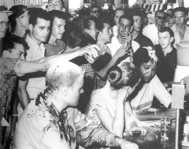 An African American woman sits at a lunch counter with hands folded. beside her are two white patrons, man and woman. The woman's head is turned to talk to the African American woman. All three appear to have had coffee and sugar dumped on them. A white man is in the act of dumping sugar on the white woman's head.