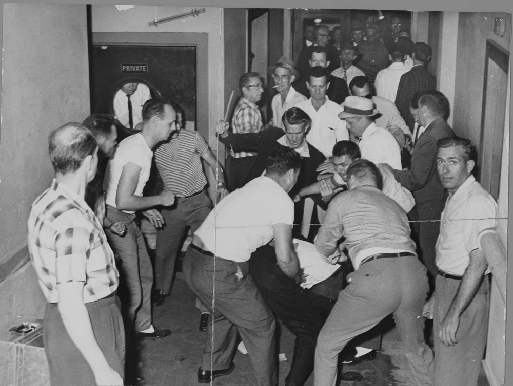 A group of four white men beat a man who is bent over in the picture. Other white men stand around watching. One is looking directly at the camera.