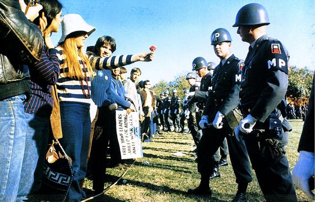 A young female college student extends her arm holding a flower in her hand. Other students lined on either side of her look on. Opposite her is a line of military police with batons in hand. They are standing still and appear to ignore the gesture.