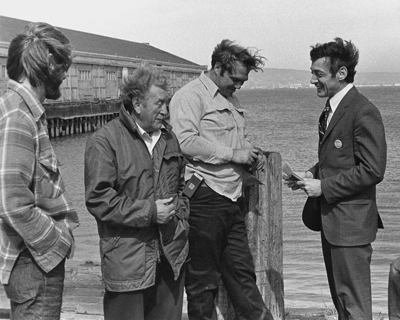 Four men in conversation on a pier in California. The man on the right (Milk) is dressed in a suit. The other 3 are dressed in working attire.