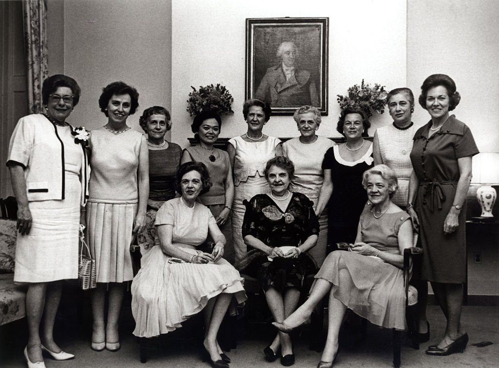 Twelve women pose for a formal picture inside a congressional office.