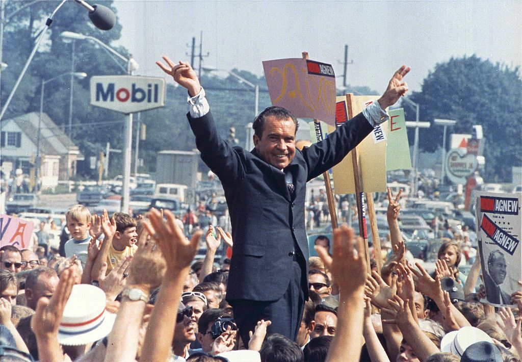 A man in a suit (Nixon) smiles as he stands above a crowd of people on a city street with his arms raised in the air. His fingers create a 'V' in each hand. Many in the crowd have their hands raised in the air as well.