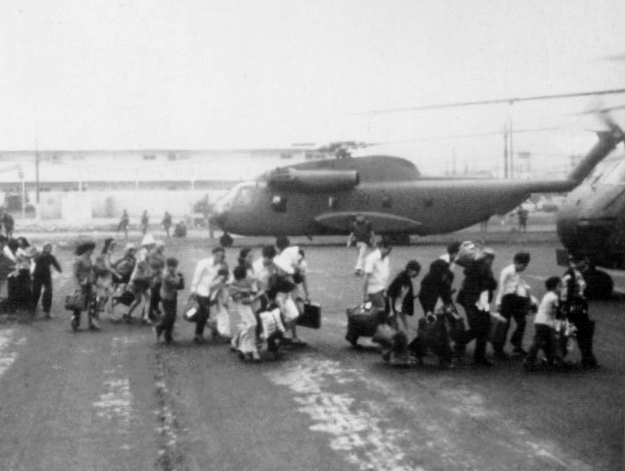 A line of people hurry toward a helicopter with baggage in hand.