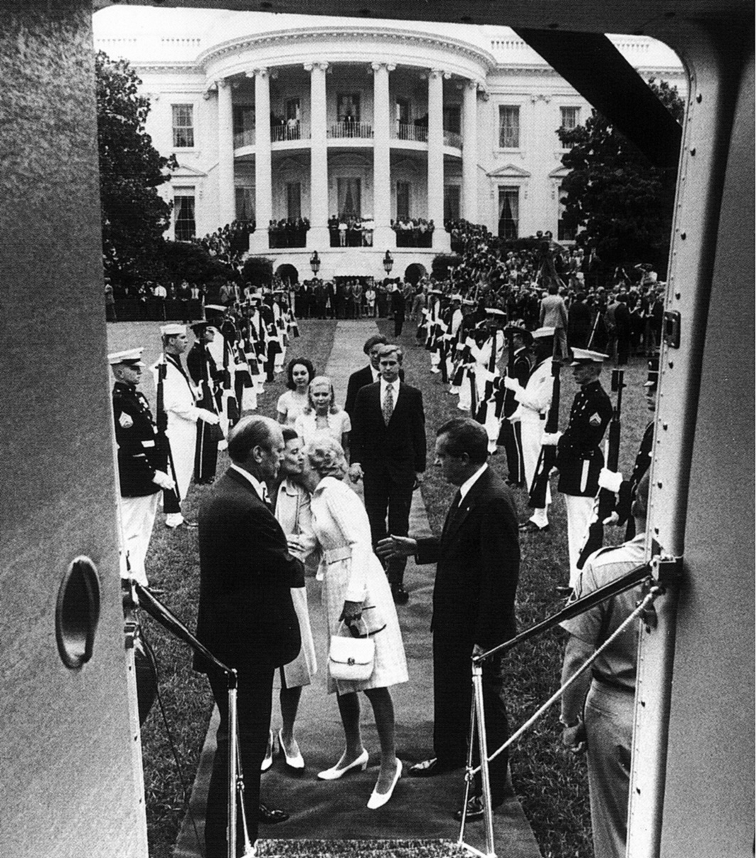 View is from inside the aircraft looking toward the White House. Soldiers stand at attention forming two lines from the White house to the aircraft. Mrs. Nixon is kissing Mrs. Ford on the cheek as she prepares to come aboard. Presidents Nixon and Ford look on.