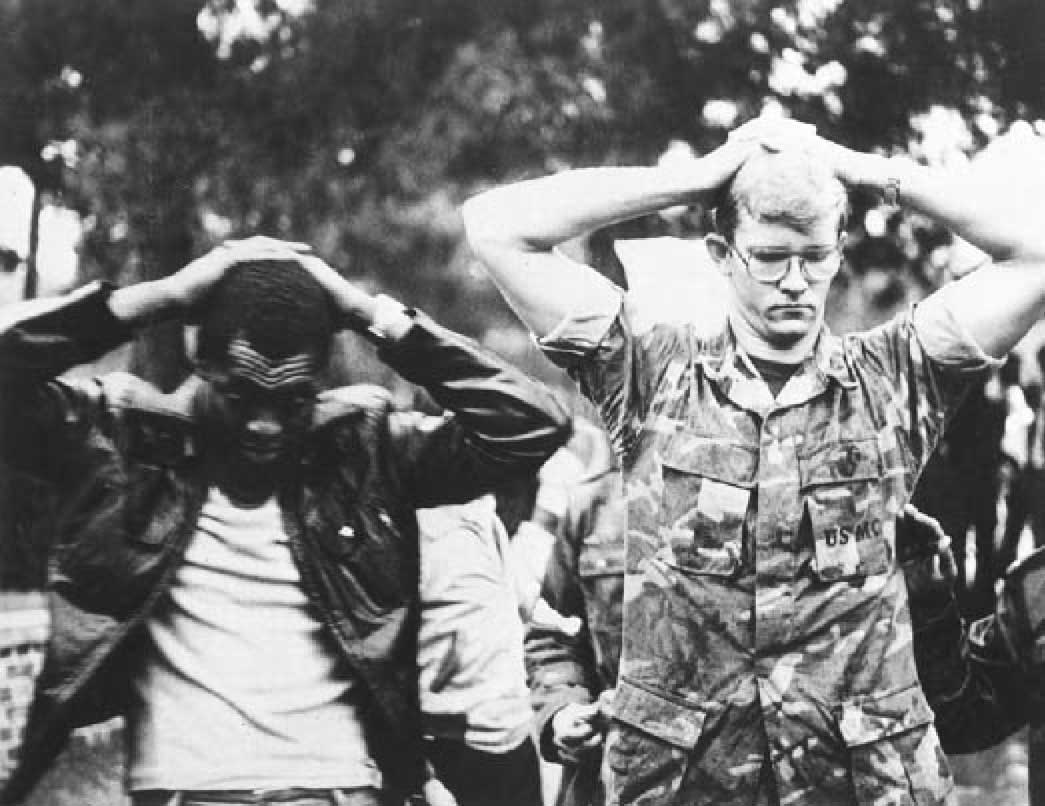Two men, one African America wearing a white t-shirt and leather jacket, and one white wearing a camouflage USMC uniform stand with their hands behind their heads.