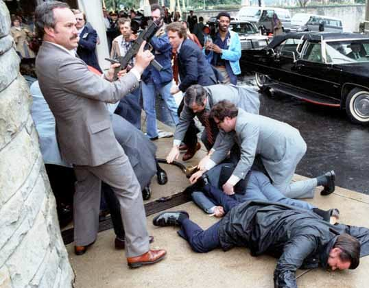 Panicked scene outside a building. Two men in business suits lie face down on the ground while two others provide aid. Another man in a suit stands guard with a semi-automatic weapon raised into the air. Reporters and bystanders crowd the background.
