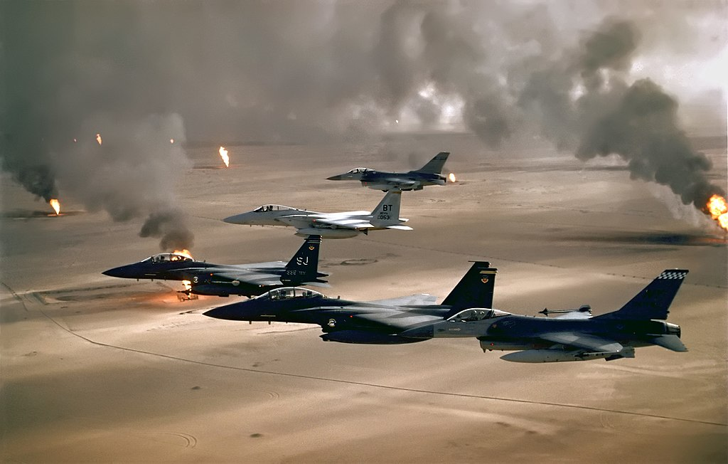 Five jet aircraft in flight over flat terrain. The terrain has multiple spouts of fire coming from the ground and spewing thick black smoke.