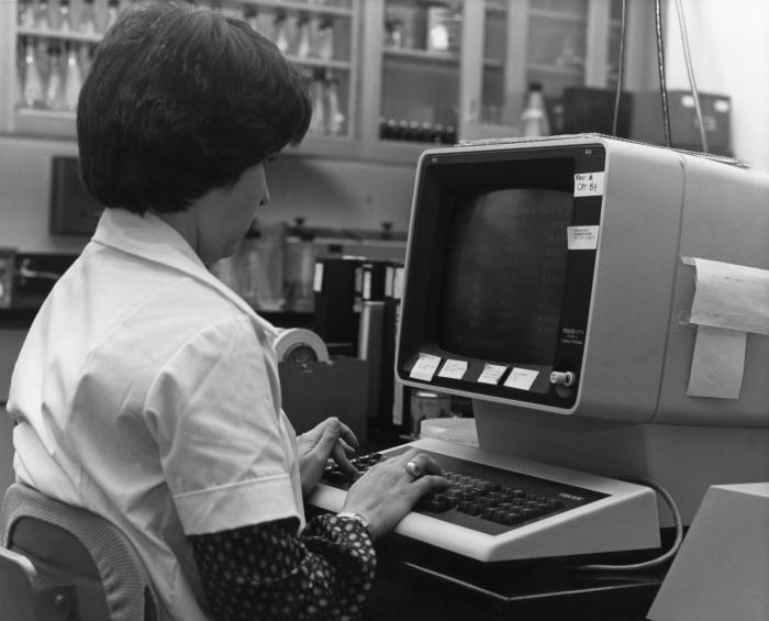 Young woman with her fingers on the keyboard of a large CRT console.