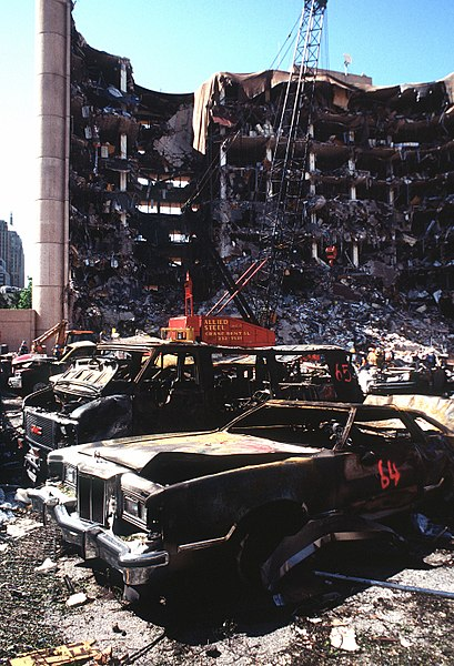 The bombed remains of automobiles with the bombed Federal Building in the background.