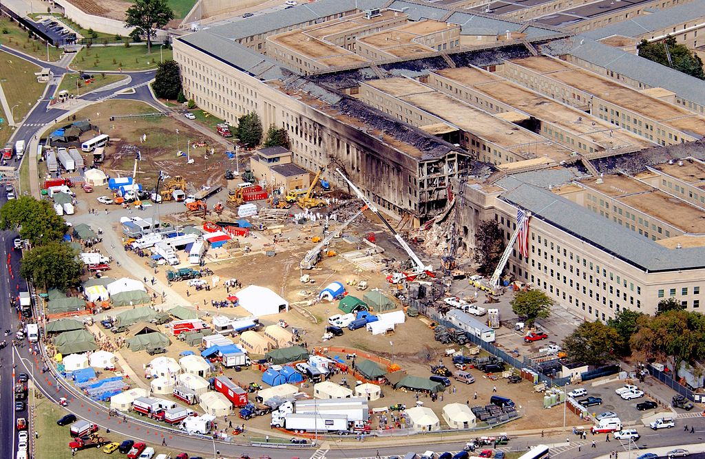 A close-up of one wall of the Pentagon show a large burned out area on the outer ring and complete destruction of a section of that ring. The roof is nearly burned away. An American flag hangs on the right side of the destroyed area. Next to the Pentagon building, a rescue operations site is in progress. Many tents, tractor trailers, cranes, and trucks surround this part of the building. People in hazardous materials (Haz Mat) suits and boots walk among the wreckage.